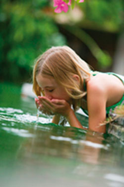 Little girl drinks water from a pond