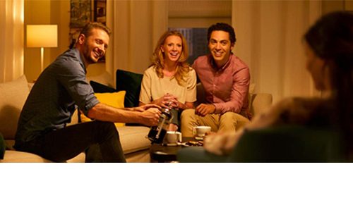 People enjoying the warm glow of a dimmed light bulb in a living room