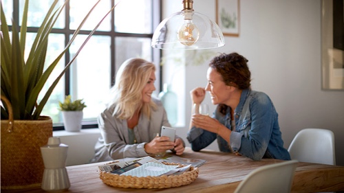 Two women at home talking underneath a Philips light bulb