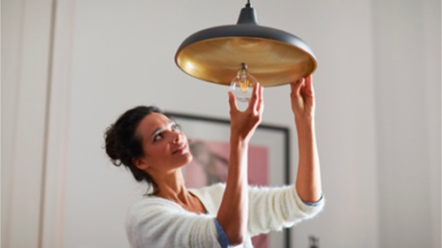 Woman screwing in a consumer light bulb at home