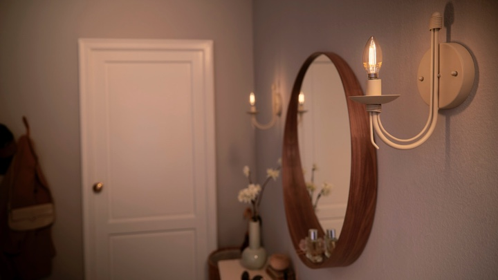 Candle bulbs on both sides of a hallway mirror